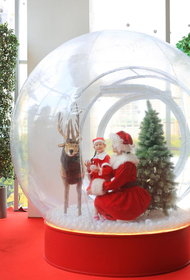 Happy little child girl and mother in santa costume dress has fun in big winter Snow globe with reindeer on christmas time. Merry. Xmas and happy new year royalty free stock photos