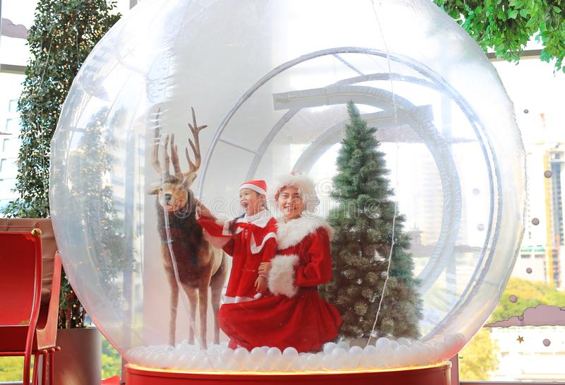 Happy little child girl and mother in santa costume dress has fun in big winter Snow globe with reindeer on christmas time. Merry. Xmas and happy new year royalty free stock photo