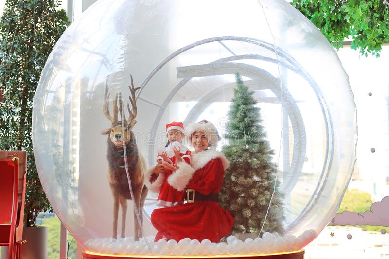 Happy little child girl and mother in santa costume dress has fun in big winter Snow globe with reindeer on christmas time. Merry. Xmas and happy new year royalty free stock image