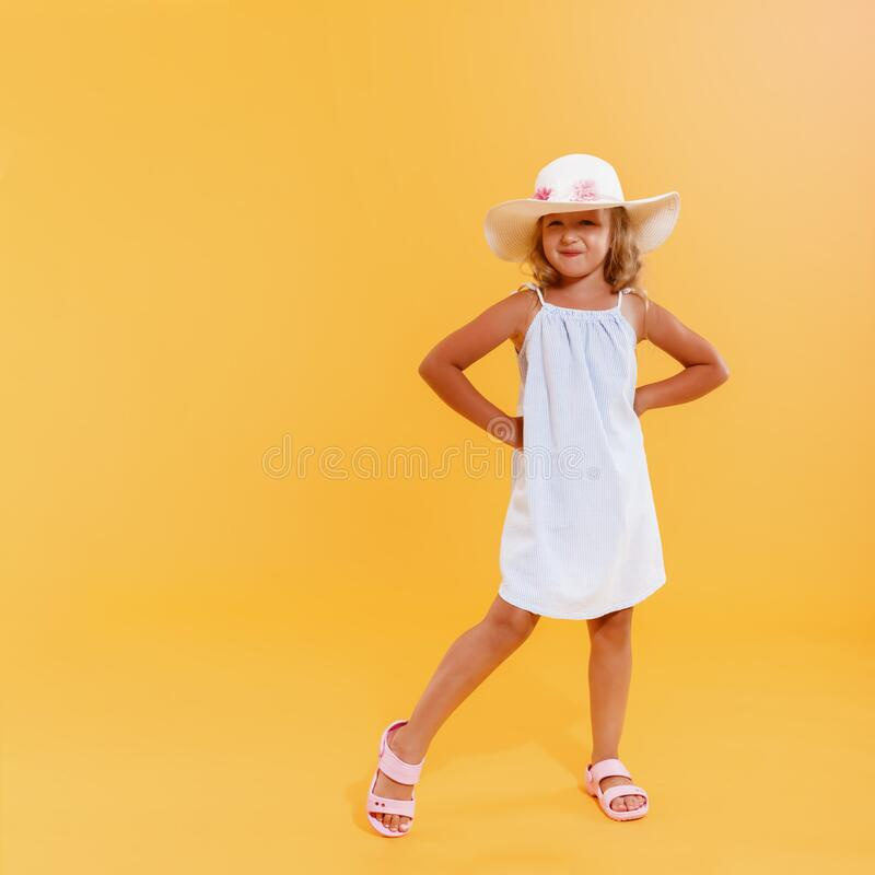 Happy little child girl preschooler  standing in full growth in a hat and summer sundress on a yellow background stock image