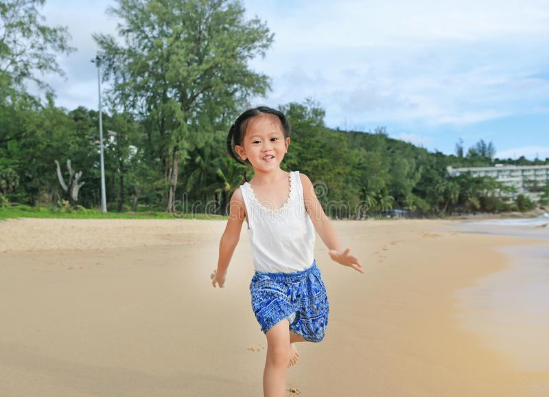 Happy little child girl running on the beach in summer times.  royalty free stock images