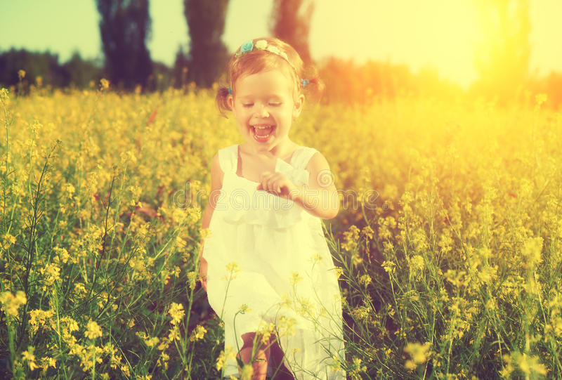Happy little child girl running on field with yellow flowers. Happy little child girl in a white dress running on field with a bouquet of yellow flowers royalty free stock photo