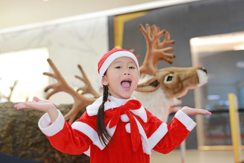 Happy little child girl in santa costume dress on winter time against reindeer christmas background. Merry Christmas and happy. New year stock photos
