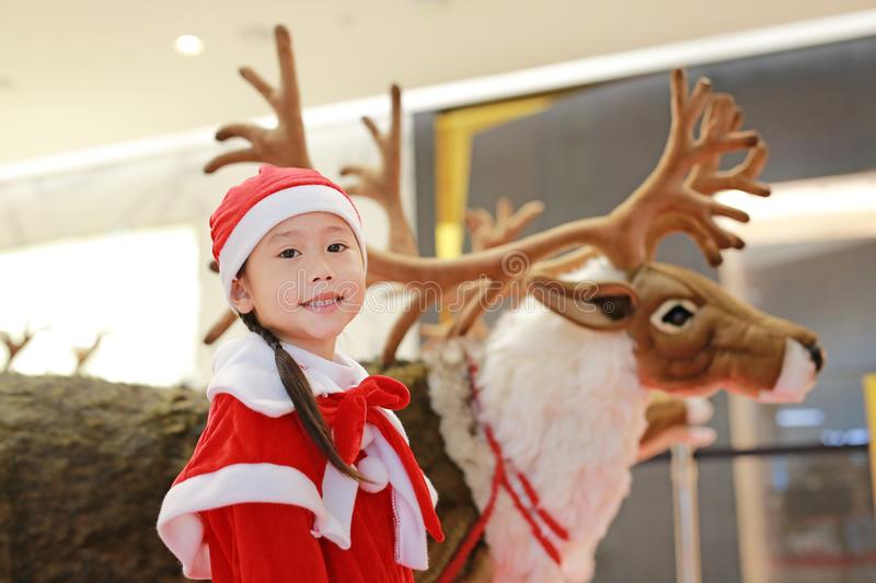 Happy little child girl in santa costume dress on winter time against reindeer christmas background. Merry Christmas and happy. New year royalty free stock photography