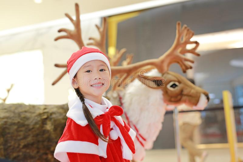 Happy little child girl in santa costume dress on winter time against reindeer christmas background. Merry Christmas and happy ne. W year royalty free stock images