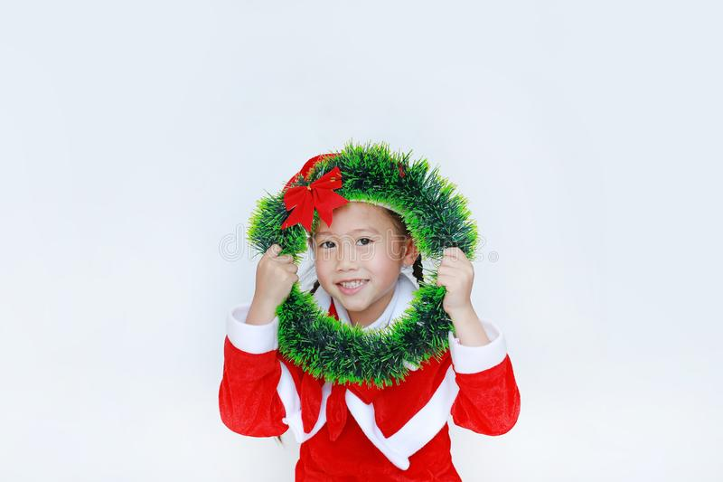 Happy little child girl in Santa costume with holding Christmas round wreath on her face on white background. Merry Christmas and stock photo