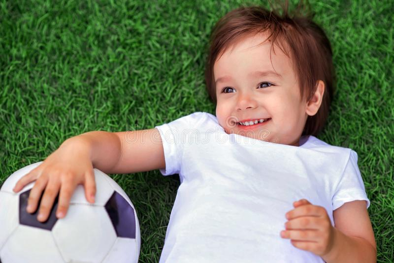 Happy little child laying on a green football field holding soccer ball and smiling. Future football star and little sportsman. Concept stock image