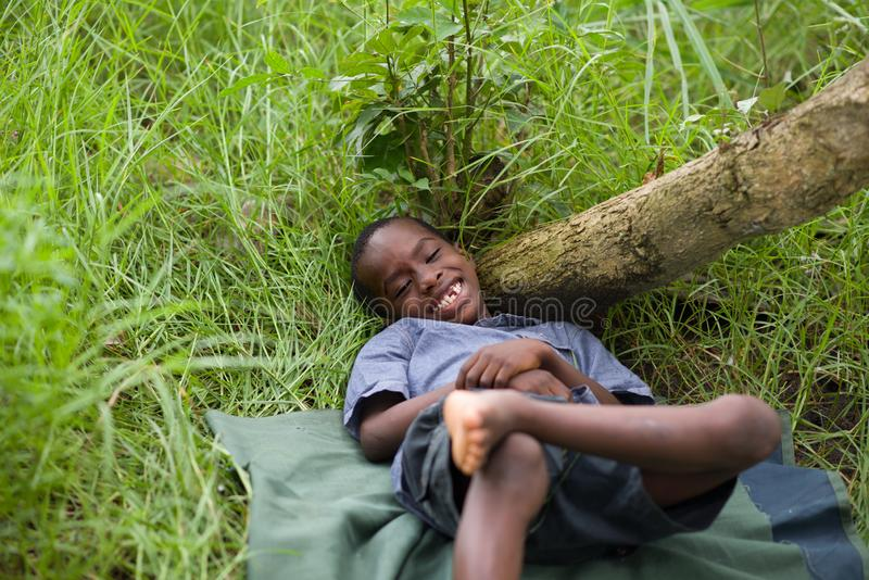 Happy little child lying on the grass stock photo