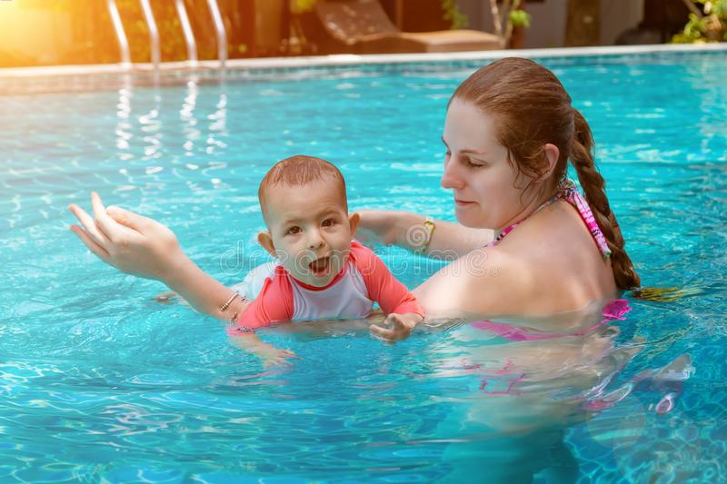 Happy little child with mother, Baby first time in a large pool and very impressed. Infant very happy, with open mouth, Teaching royalty free stock photos