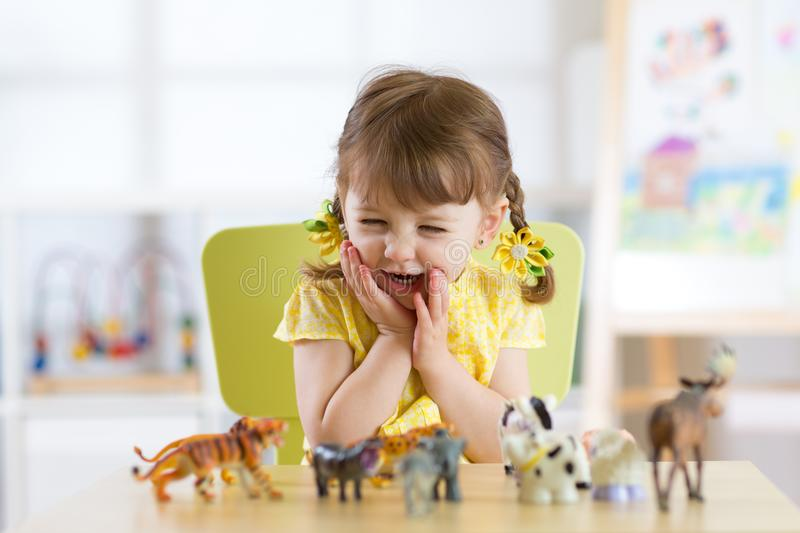 Happy little child plays animal toys at home or daycare centre royalty free stock photos