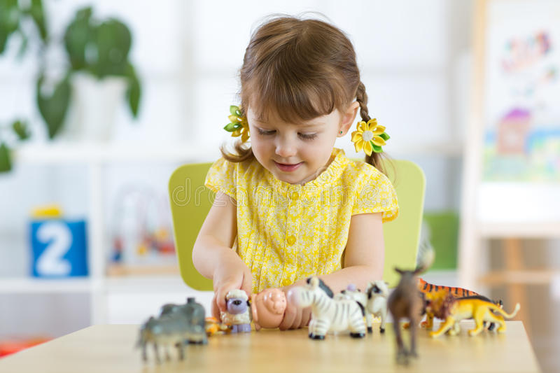 Happy little child plays animal toys at home or daycare. Centre royalty free stock photo