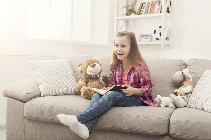 Happy little child reading book for her teddy bear royalty free stock image