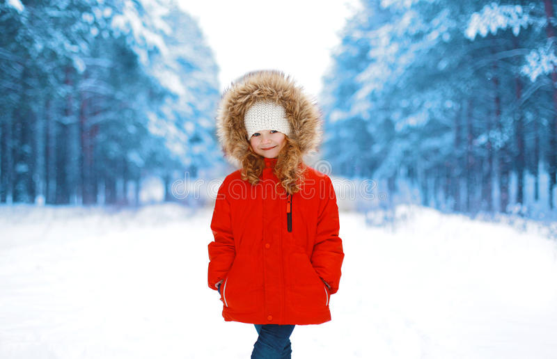 Happy little child in red jacket outdoors in winter. Snowy forest stock photography