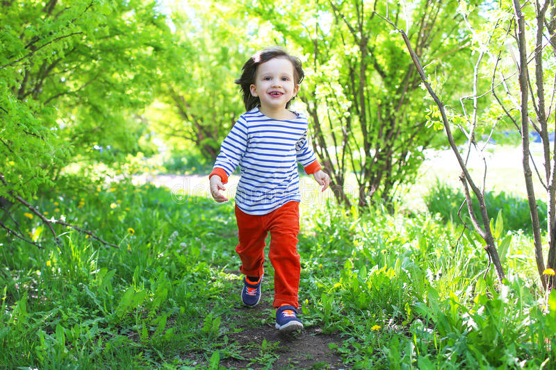 Happy little child running outdoors in summertime. Happy little child running in summer royalty free stock photo