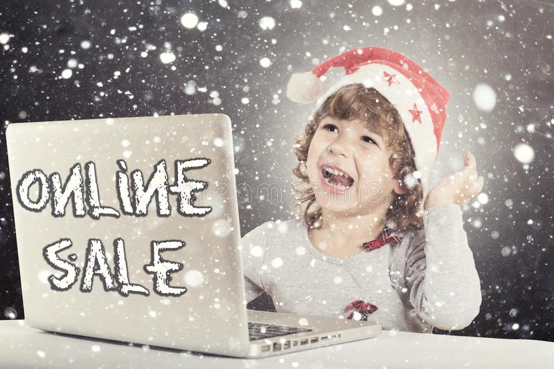 Happy little child. With Santa hat and laptop computer,holiday online sale royalty free stock photography