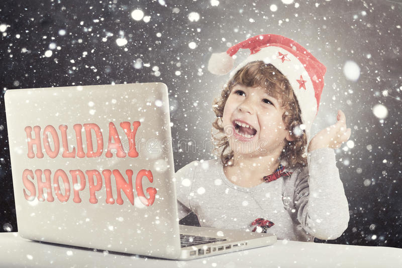 Happy little child. With Santa hat and laptop computer and holiday shopping sign,selective focus stock photos