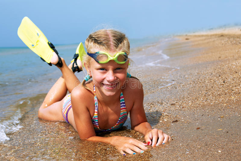 Happy little child smiling on summer beach sand. With snorkel equipment looking to side at copy space after swimming with fins and mask on vacation royalty free stock photography