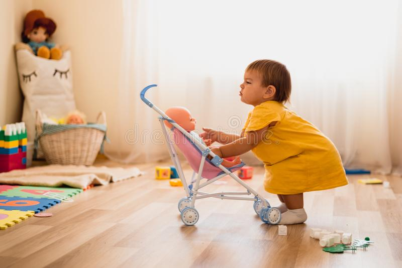 Happy little child toddler girlplaying with stroller with baby doll indoors at home or daycare royalty free stock images