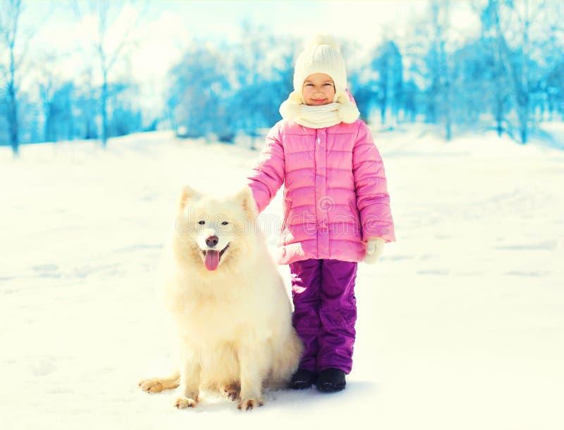 Happy little child and white Samoyed dog winter stock photo