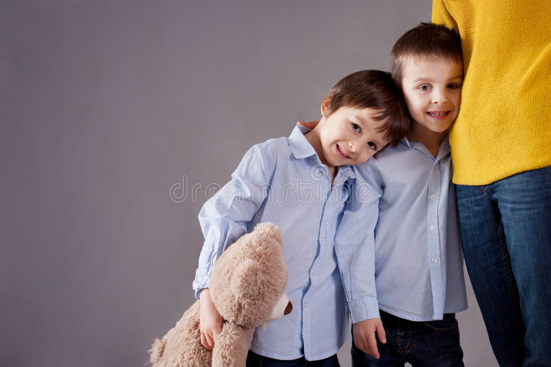 Happy little children, boys, hugging their mother at home, isolated image, copy space. Family concept stock images