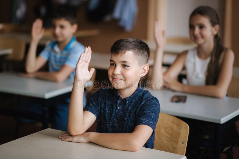 Happy little children in elementary school. Boys and girls study. Children raise hand up royalty free stock photo