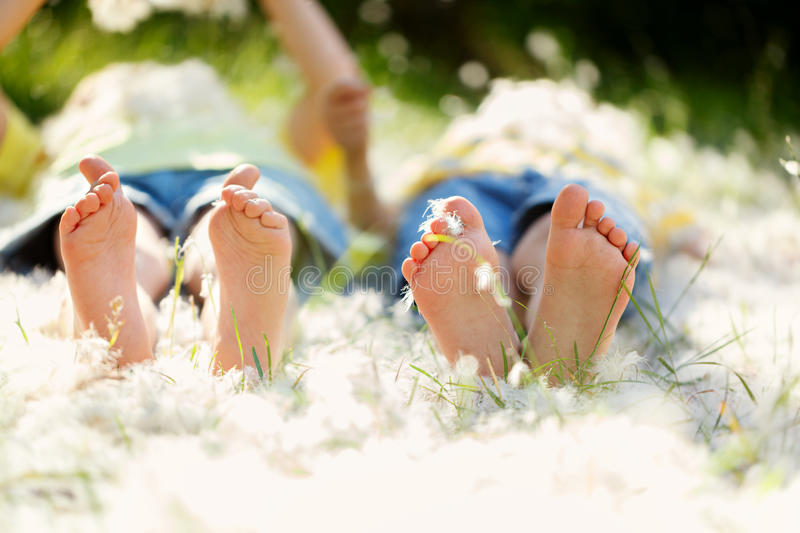 Happy little children, lying in the grass with feathers , barefoot, playing happily, childhood happiness concept. stock photo