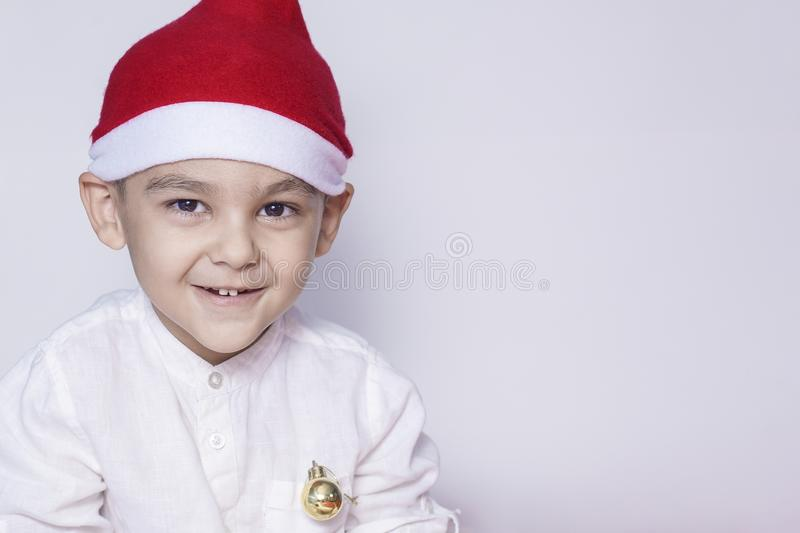 Happy little christmas boy. Celebrating Christmas. 6-7 year old kid with Santa hat stock photography