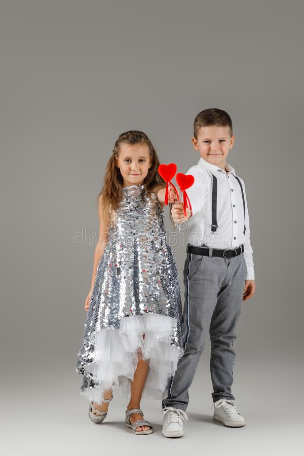 Happy little couple girl and child boy holding red hearts. Happy little couple fashionable girl in silver dress and stylish child boy holding red hearts on stick royalty free stock photography