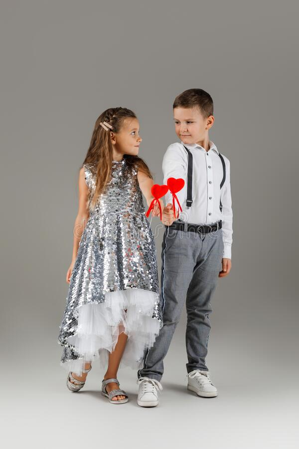 Happy little couple girl and child boy holding red hearts. Happy little couple fashionable girl in silver dress and stylish child boy holding red hearts on stick royalty free stock photo