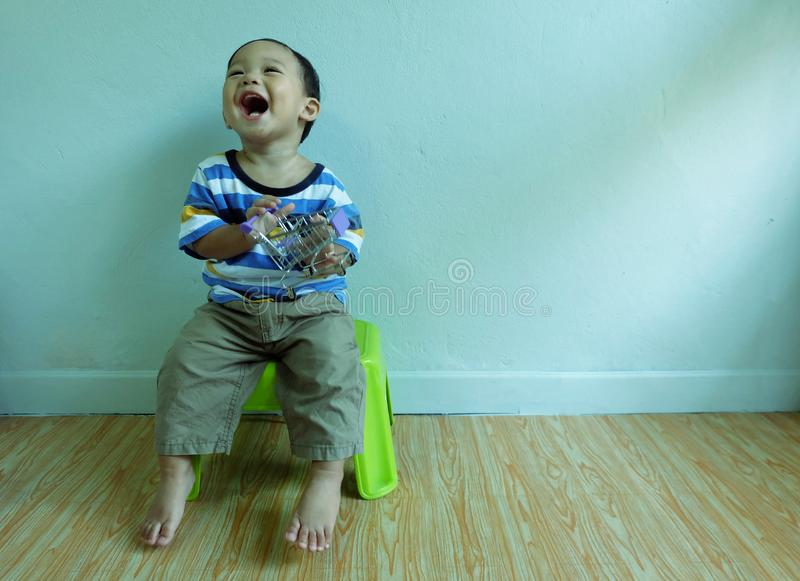 Happy little cute asian boy is wearing colorful shirt sitting on a chair smiled and laughed royalty free stock photos