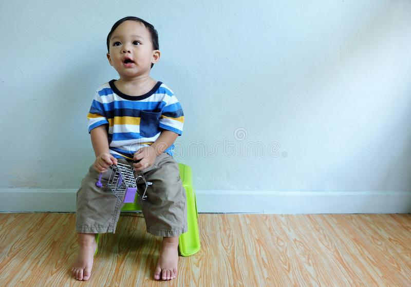 Happy little cute asian boy is wearing colorful shirt sitting on a chair smiled and laughed stock photography