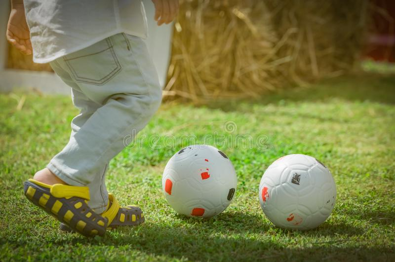 Happy little cute boy playing soccer outside home or school in summer day. Preschool kid play football in green grass lawn. Child. With casual shoes play sport royalty free stock photography