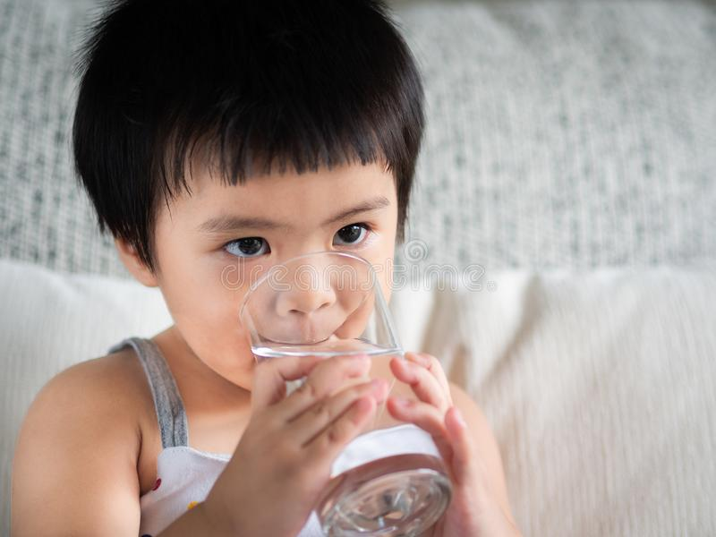 Happy little cute girl holding a glass and drinking the water. C. Hildren Drink Healthy Concept stock image