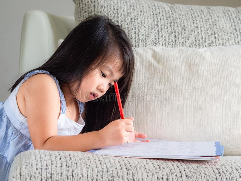 Happy little cute girl is writing the book with red pencil on th royalty free stock photos