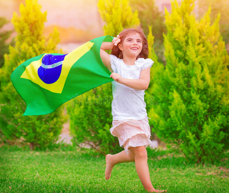 Happy little football fan. Cute little girl running on the park with national Brazil flag waving on the wind, sportive childhood, football championship concept stock photo