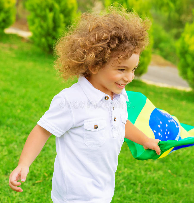 Happy little football fan. Portrait of cute little boy running with Brazil national flag, cheerful young football player, fan of Brazilian football team royalty free stock images