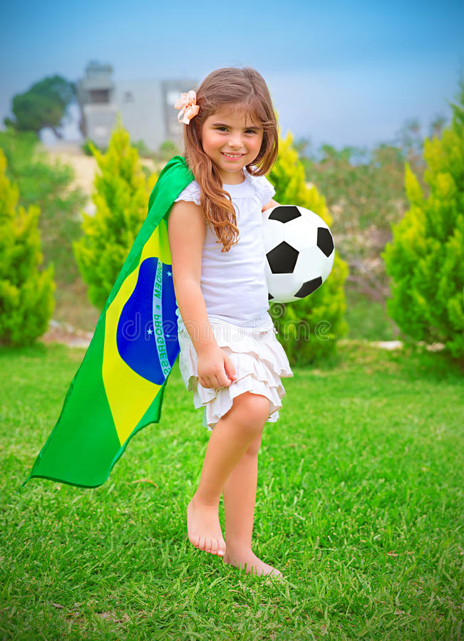 Happy little football player. Happy cheerful girl playing with ball on backyard in sunny day, big national Brazil flag, football championship concept stock photo
