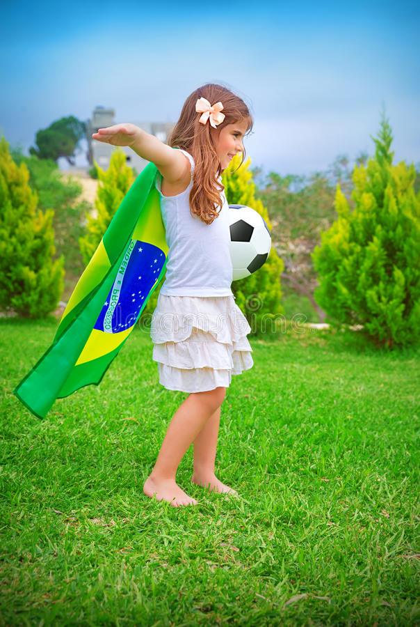Happy little football player. Happy cheerful girl playing with ball on backyard in sunny day, big national Brazil flag, football championship concept stock images
