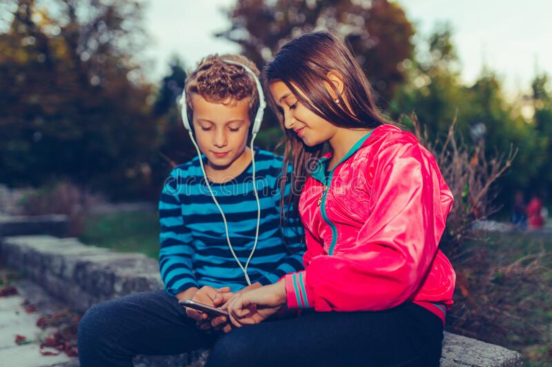 Happy little friends, boy and girl with headphones sharing music from a smart phone outdoor stock photo