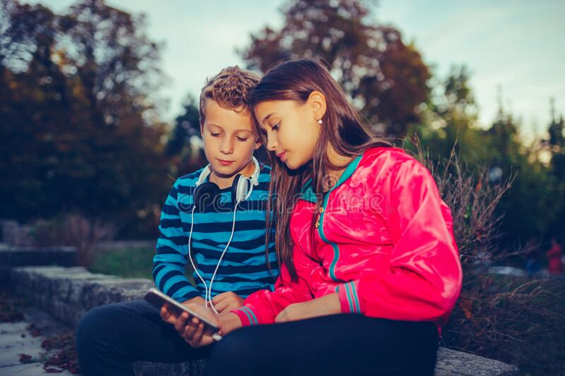 Happy little friends, boy and girl with headphones sharing music from a smart phone stock image