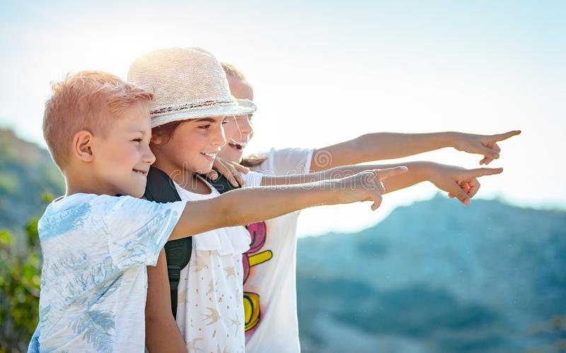 Happy little friends traveling together. Portrait of a three happy friends outdoors, kids with wonder looking at the view, with excitement enjoying amazing stock image