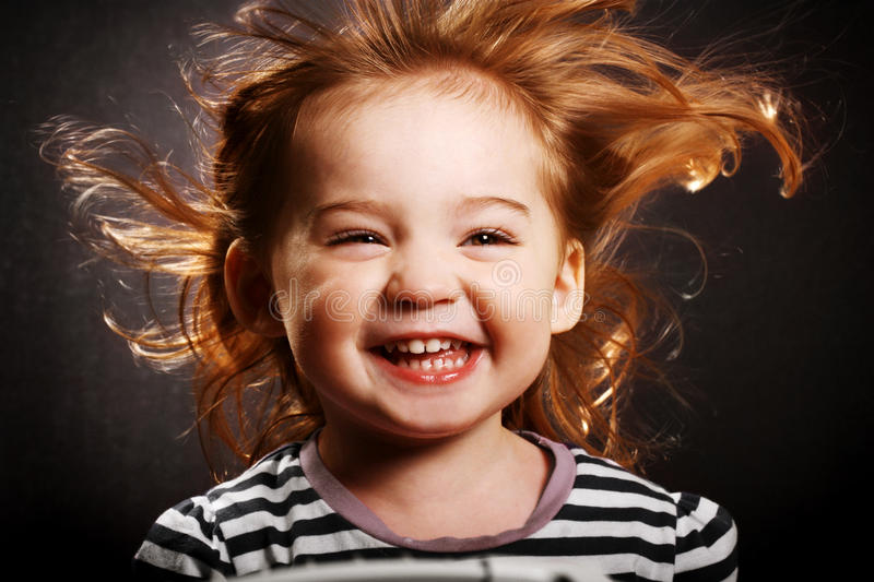 Happy little girl. A gorgeous little girl smiling hysterically with the wind in her hair royalty free stock image