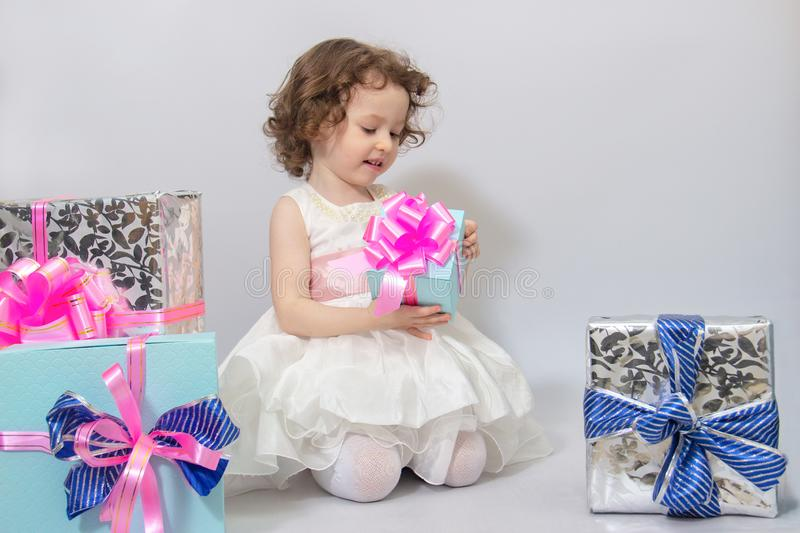Happy little girl, adorable toddler in a white dress, holding many birthday or christmas presents, opening boxes decorated with. Pink ribbon. celebrate a family stock photos