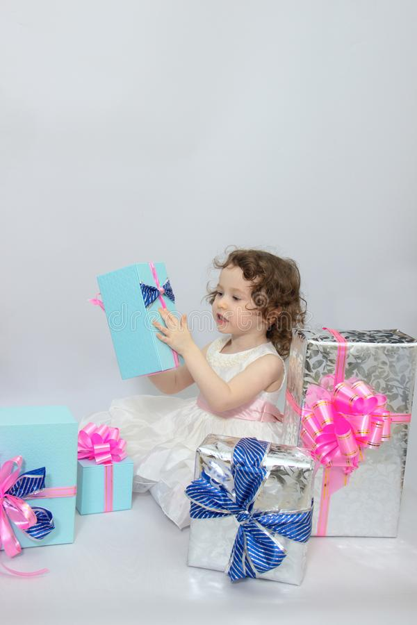 Happy little girl, adorable toddler in a white dress, holding many birthday or christmas presents, opening boxes decorated with. Pink ribbon. celebrate a family stock image