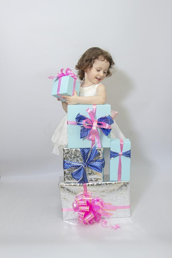 Happy little girl, adorable toddler in a white dress, holding many birthday or christmas presents, opening boxes decorated with. Pink ribbon. celebrate a family royalty free stock photos