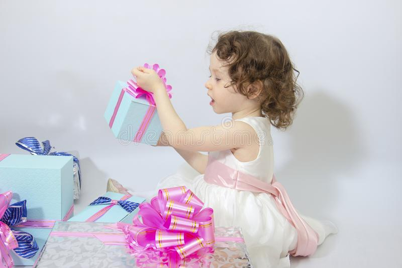 Happy little girl, adorable toddler in a white dress, holding many birthday or christmas presents, opening boxes decorated with. Pink ribbon. celebrate a family stock photography