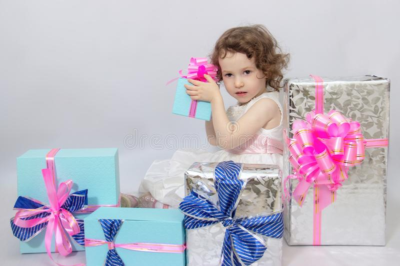 Happy little girl, adorable toddler in a white dress, holding many birthday or christmas presents, opening boxes decorated with. Pink ribbon. celebrate a family royalty free stock image