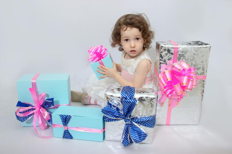 Happy little girl, adorable toddler in a white dress, holding many birthday or christmas presents, opening boxes decorated with. Pink ribbon. celebrate a family royalty free stock photography