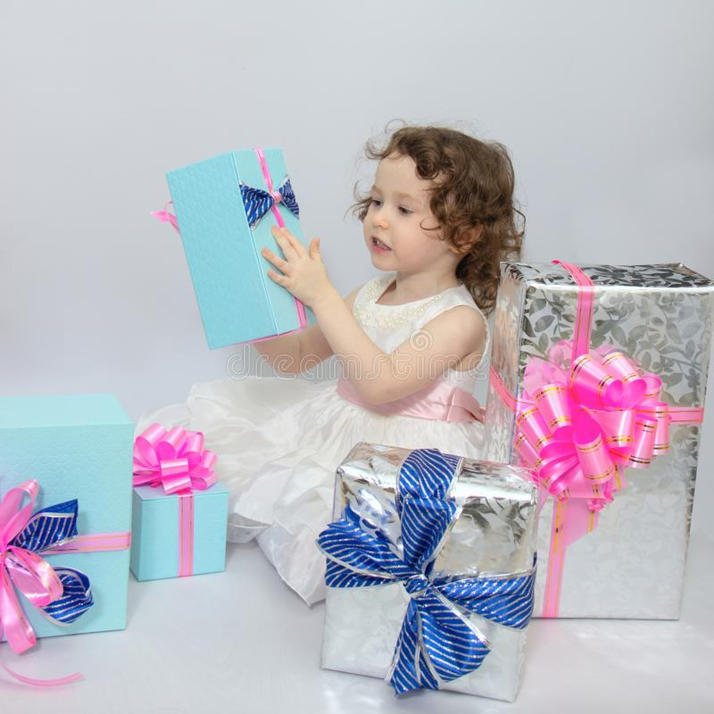 Happy little girl, adorable toddler in a white dress, holding many birthday or christmas presents, opening boxes decorated with. Pink ribbon. celebrate a family stock images