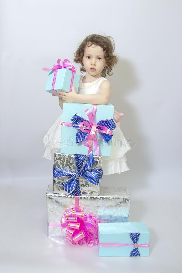 Happy little girl, adorable toddler in a white dress, holding many birthday or christmas presents, opening boxes decorated with. Pink ribbon. celebrate a family stock photo